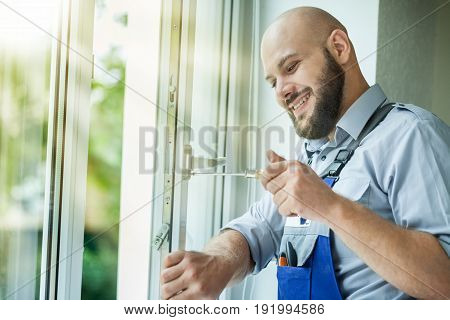 Man frame window repairman fixing green white