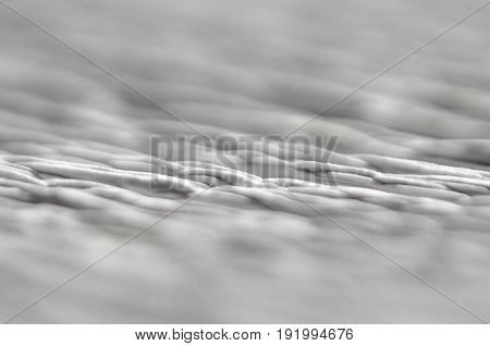 White texture of embossed paper. Macro. Shallow depth of field. Abstract background with deep grooves in the texture of corrugated paper