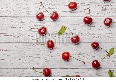 Sweet Fresh Cherries In A Bowl And Scattered And Kitchen Squared Napkin On White Rustic Wooden Backg