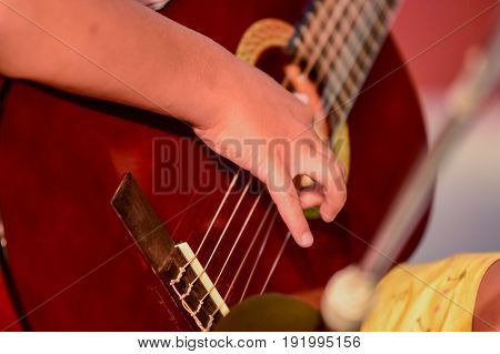 young boy plays guitar, concert, athens, greece