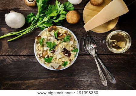 An overhead photo of a mushroom risotto, with champignons, fresh parsley, porcini, a slice of Parmesan, a glass of white wine, a fork and a spoon, and a place for text, on a dark rustic texture