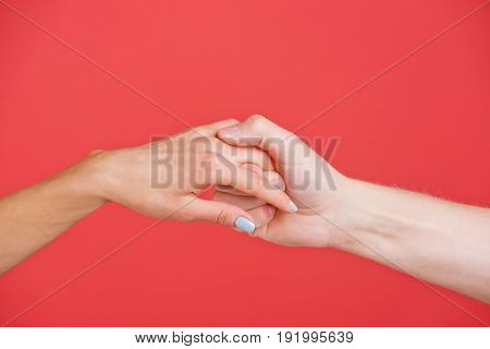 hands of man and woman hold each other on red background help and faith
