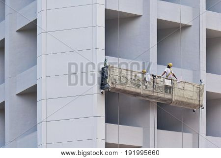 Construction workers in lift hanging from the building