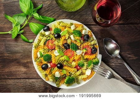 A photo of a plate of pasta salad with basil leaves, olive oil, and a glass of rose wine, shot from above on a rustic texture with a fork, spoon, and a place for text