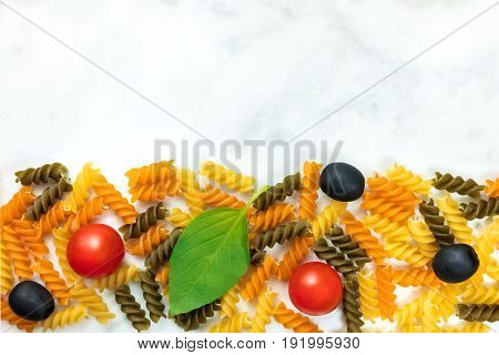 Pasta salad ingredients on white marble with a place for text. Rotini, cherry tomatoes, fresh basil leaves, and black olives
