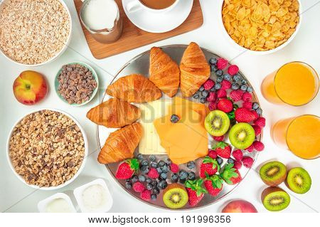 Overhead photo of a continental hotel breakfast on white background. An assortment of croissants, cheese, fresh fruit, orange juice, cereal bowls, coffee with milk and cane sugar, and yogurt cups