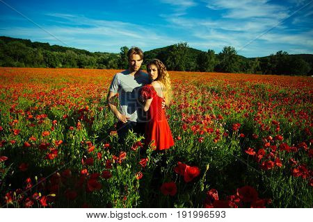 Woman And Guy With Flower Bouquet In Red Poppy Field