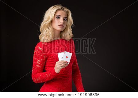 Young beautiful emotional woman with cards in hands on a black background in the studio. Portrait of a beautiful blonde in a red dress. Poker