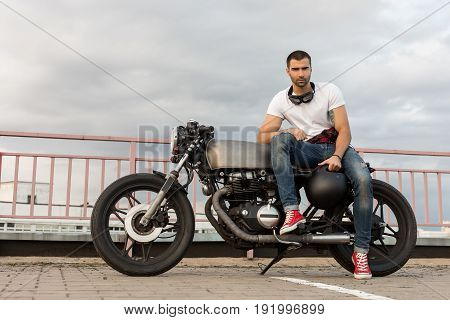 Brutal Man Sit On Cafe Racer Custom Motorbike.