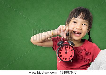 Girl holding a alarm clock on green chalkboard copy space