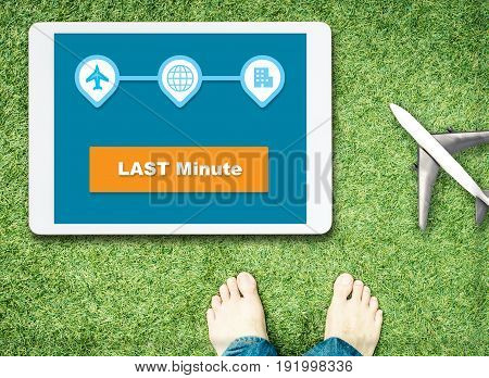 Last minute booking on tablet screen with grasses and barefoot for Relax vacation concept