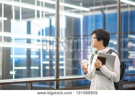 Young Asian university student holding laptop and coffee cup study and learning lifestyle in college with international education concepts