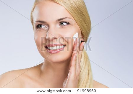 Young Happy Woman Applying Cream On Face Looking Away
