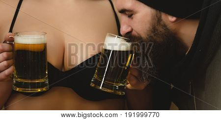 man or brutal hipster with long beard and moustache drinking beer from glass mugs in waitress hands on sexy female breast or bust in black bra background. Alcohol bad habits and addictive