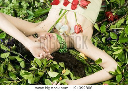 Pretty Woman With Fashionable Makeup With Flowers On Green Leaves
