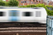 Fast commuter train passing by during rush hour poster