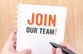 join our team word on white ring binder notebook with hand holding pencil on wood tableBusiness concept. poster
