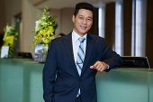 Confident Asian hotel owner with hand in pocket leaning on front desk and looking at camera with wide smile, waist-up portrait poster