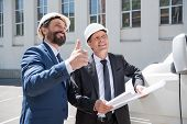 Two smiling architects in hardhats holding blueprint and showing thumb up poster