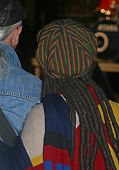 reggae style woman with dreadlocks and reggae cap rear view at a music event poster