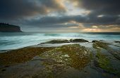 Moody clouds leave a small break for the sunrays to peak through on the low tidal rockshelf at Bilgola poster
