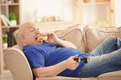 Fat senior man playing videogame and eating hamburger while lying on sofa at home. Sedentary lifestyle concept poster