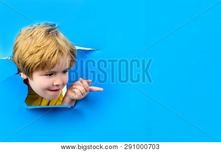 Curious Child Looks Through Hole Paper. Boy Peeking From Ripped Paper Hole. Surprised Kid Points On