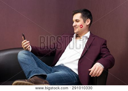 Young Playboy Lover With Lipstick Makes A Photo On A Smartphone  A Man With Lipstick On A Cheek Kiss