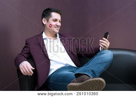 Young Playboy Lover With Lipstick Makes A Photo On A Smartphone. A Man With Lipstick On A Cheek Kiss