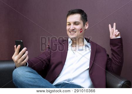 A Man With Lipstick On A Cheek Kiss. Young Playboy Lover With Lipstick Makes A Photo On A Smartphone