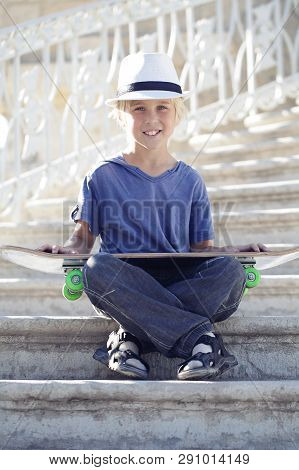 Skater Boy With Blue T-shurt Sitting With A Longboard