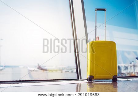 Isolate Traveler Tourist Yellow Suitcase At Floor Airport On Background Large Window, Bright Luggage