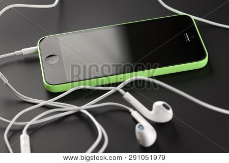 Tambov, Russian Federation - October 16, 2013: Apple Iphone 5c Green Color, Apple Earpods On Black B