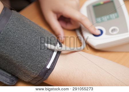 Woman Checking Blood Pressure And Heart Rate With A Digital Blood Pressure Monitor.