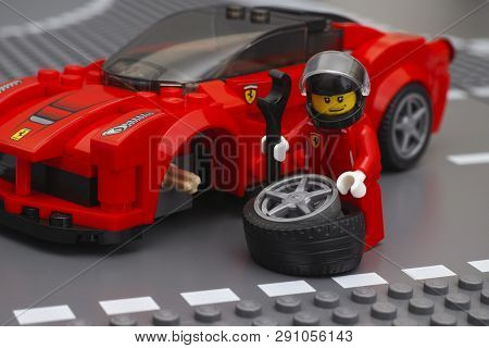 Tambov, Russian Federation - March 05, 2015 Lego Driver Minifigure Is Fixing Wheel Of Laferrari By L