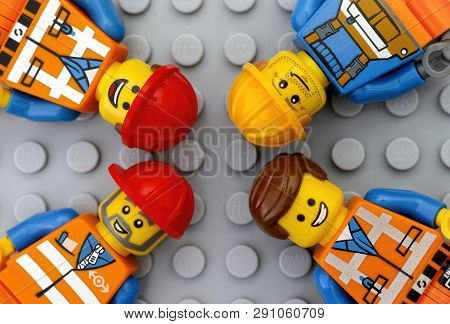 Tambov, Russian Federation - May 12, 2016 Four Lego Workers Minifigures On Lego Gray Baseplate Backg