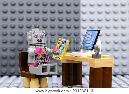 Tambov, Russian Federation - July 06, 2016 Lego Robot Minifigure With Instruction Sitting Near Compu