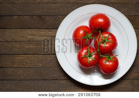 Big White Plate With Red Washed Tomatoes On It. Water Droplets On Ripened Vegetables. Top View. Clos