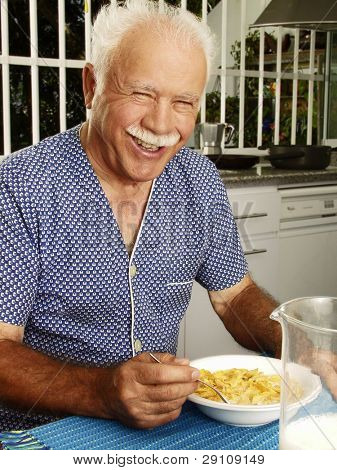 Grand father having breakfast at kitchen,Grand father eating cereal corns flakes.