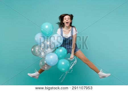 Cheerful Young Woman In Denim Clothes Keeping Mouth Open, Jumping High, Celebrating, Hold Colorful A