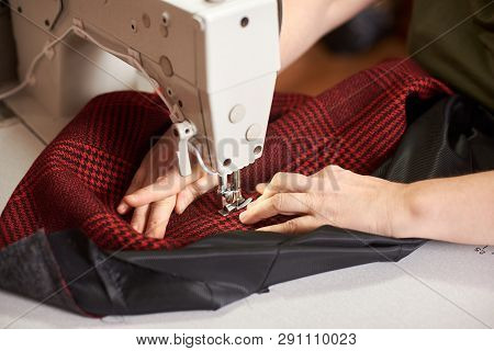 Female Hands Sewing Plaid Fabric On Professional Manufacturing Machine At Workplace. Clothier Hands