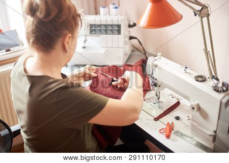 Woman sitting on her workplace in atelier. Female hands using scissors for cutting off fabric piece in sewing process. Overlock, sewing-machine, table lamp, ruler and scissors on background. Back view poster