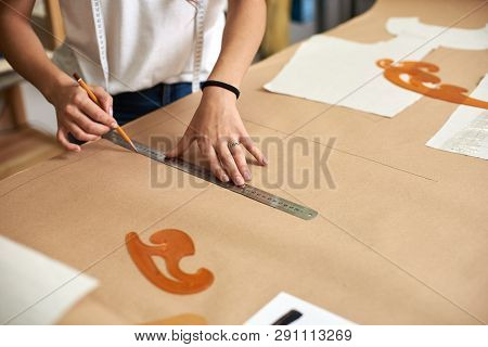 Workplace In Design Studio. Professional Female Designer Hands Close-up Making Paper Patterns Using