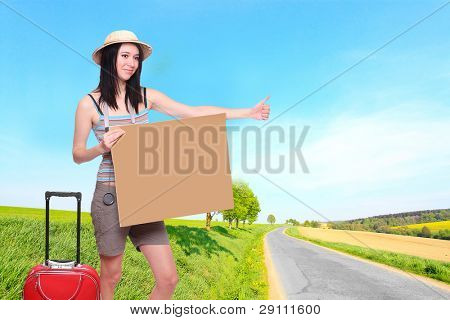 Young hiker with empty sign board on the road. Traveling concept.