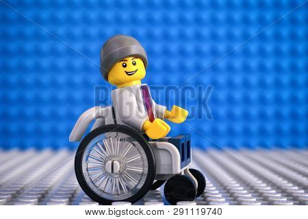 Tambov, Russian Federation - February 05, 2018 Lego Boy Minifigure In Wheelchair. Blue And Gray Base