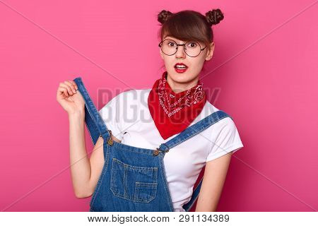 Closed Up Portrait Of Surprised Dark Haired Woman With Two Funny Baunches In Jeans Overalls, White T