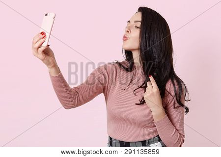 Photo Of Charming Girl Using Smartphone For Selfie. Attractive Female With Long Dark Hair Makes Self