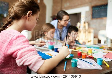 Back View Portrait Of Teenage Girl Painting Picture In Art Class With Group Of Children, Copy Space