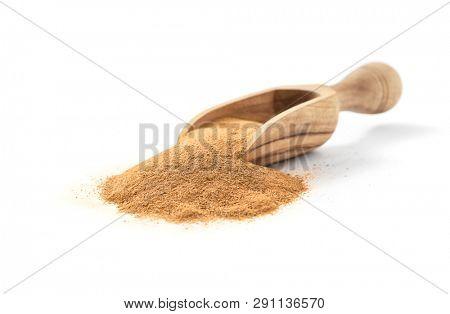 Ground ceylon cinnamon in wooden scoop on white background