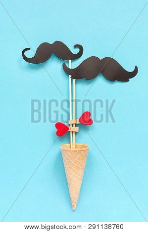 Couple Paper Mustache Props On Stick Fastened Clothespin Heart In Ice Cream Waffle Cone On Blue Back